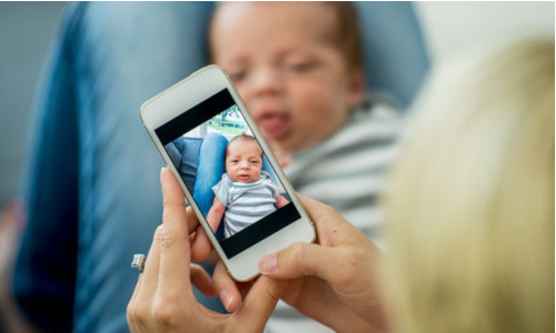 Someone taking a photo of a baby
